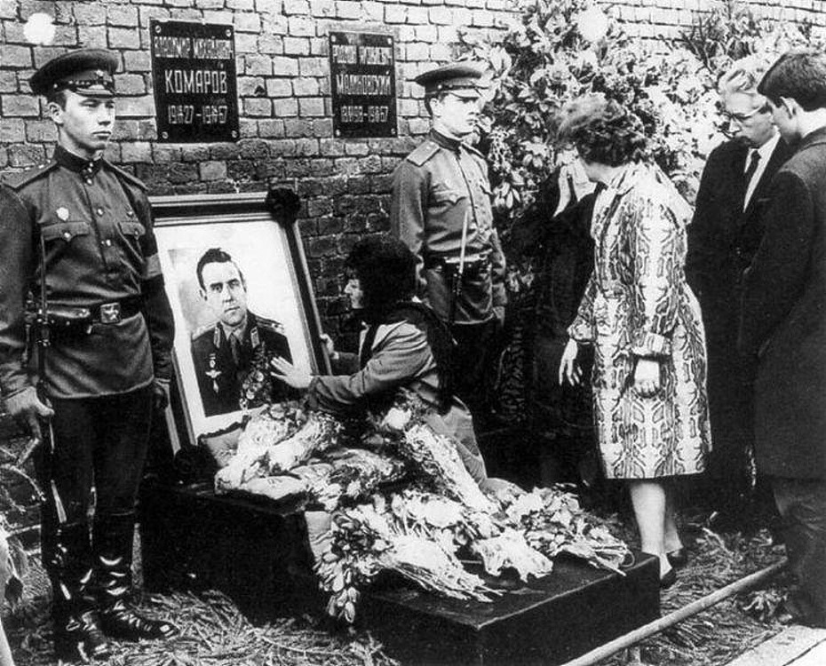 A woman in a headscarf kneels in front of a framed photo of Komarov and touches the glass. Two military guards stand next to the photo and flowers are laid out in front. Several friends stand to the side.