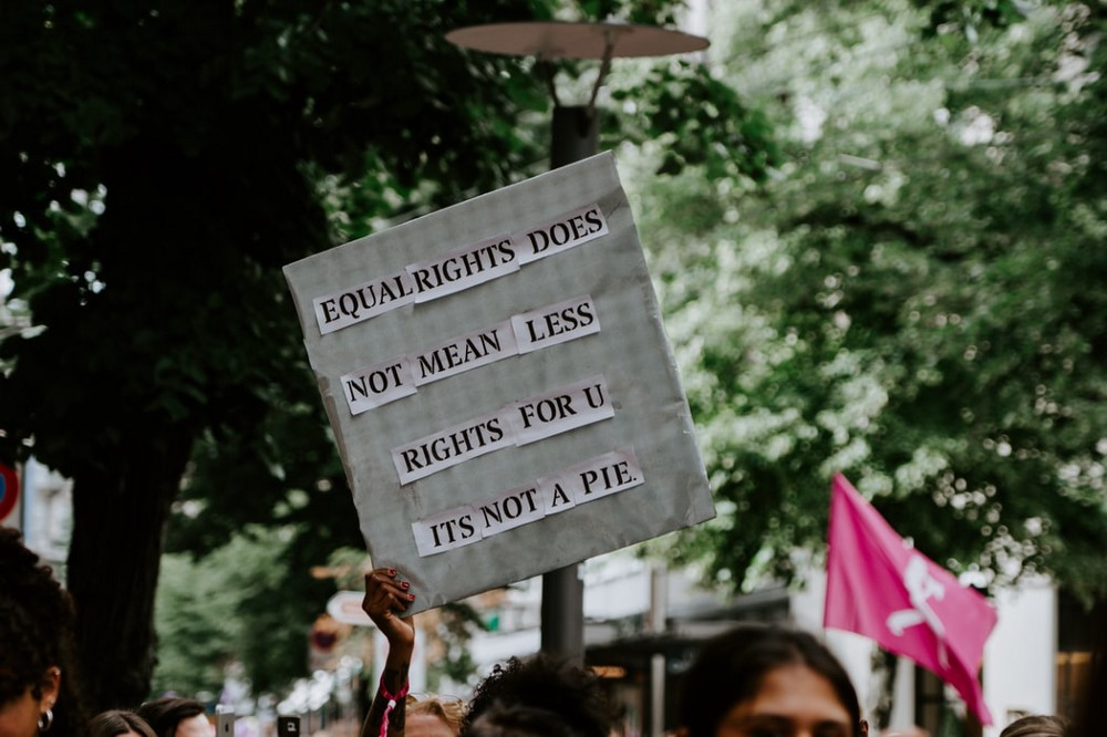 """A photo of a person in a crowd holding a sign that says, """"Equal rights does not mean less right for U. It's not pie."""""""