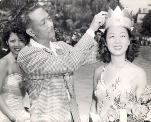 A man places a crown on Penny Lee Wong's head. Wong is smiling and holding a bouquet of flowers.
