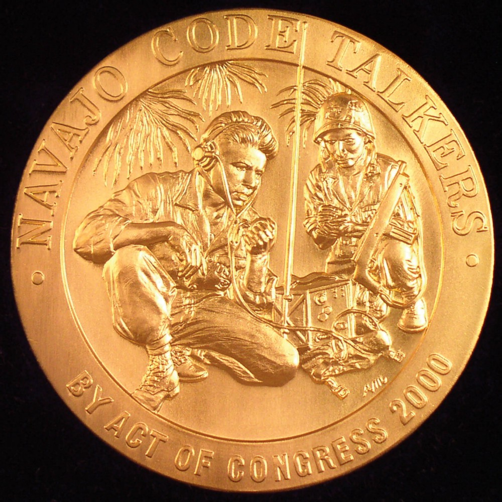 A gold medal with a depiction of two code talkers using equipment with the inscription Navajo code-talkers by act of congress 2000