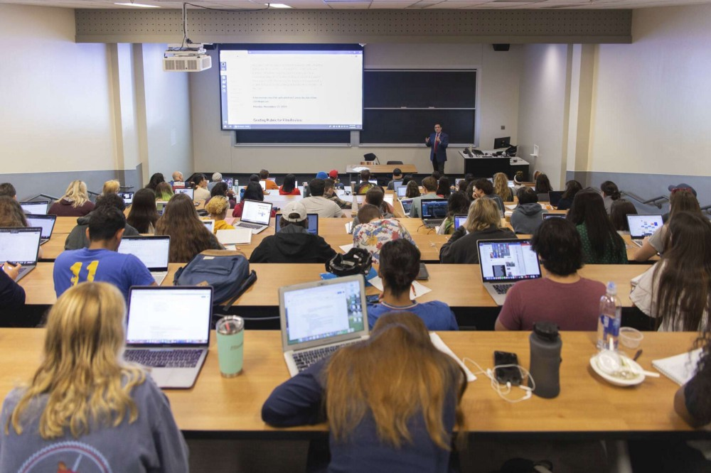 Students fill every seat of a lecture hall. Thomas Garza stands in front of them next to a screen with information on it.