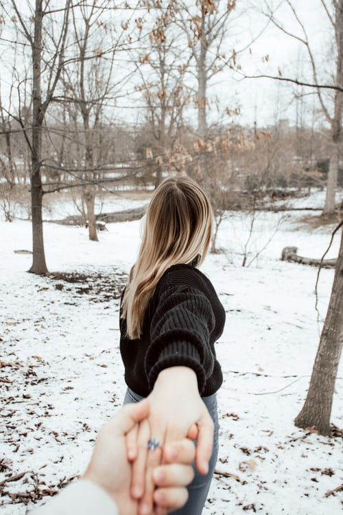 A woman with long hair is holding the hand of someone behind her, and pulling away. They are outside and snow is on the ground.