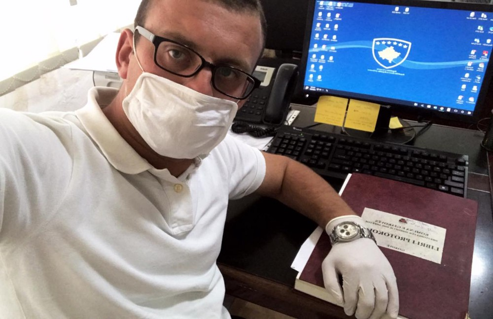 Besfort, wearing a white shirt, white facemask, white gloves, and glasses, looks at the camera, which he is holding