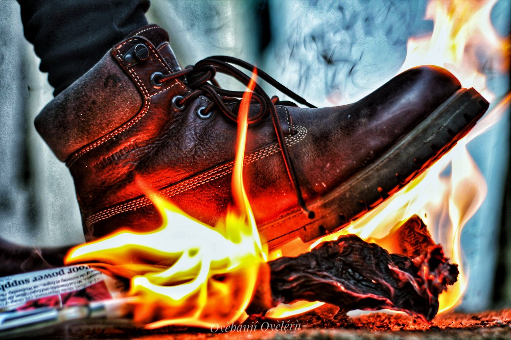 A rugged brown timberland steps on an old newspaper on fire
