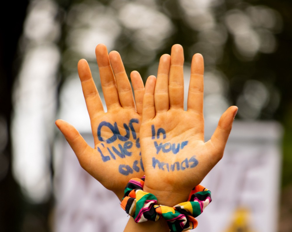"""Protester with bound hands reading """"our lives are in your hands"""""""