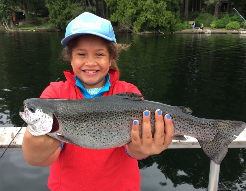 Young girl holding a rainbow trout she just caught in both her hands.