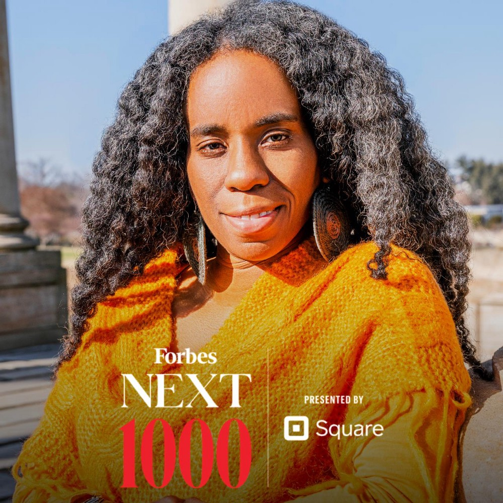 """Alyscia Cunningham with graphic that reads """"Forbes Next 1000"""". She is outdoors and wears a mustard yellow sweater throw. She smiles gently staring directly into the camera. Her hair is black and is out and wavey."""