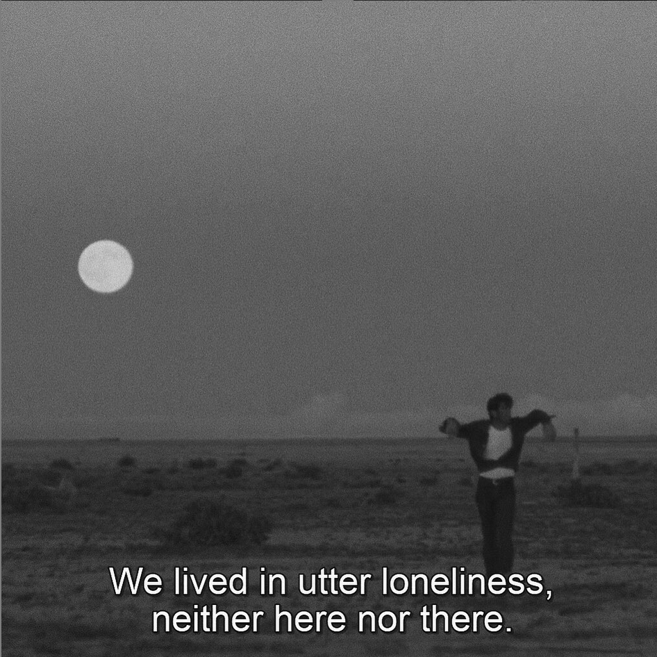 Screen shot from Badlands 1973, by Terrence Malick. A man stands in the desert at night with his arms draped lazily over a stick. The moon behind him is full and the subtitle reads: We lived in utter loneliness, neither here nor there.