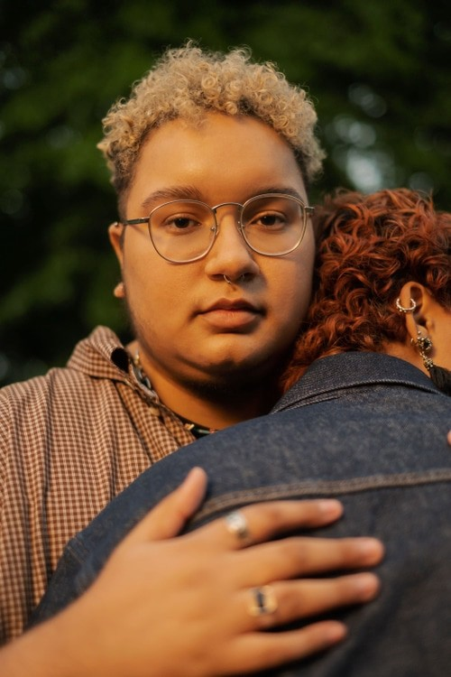 A queer person with a blank expression on their face while they hug someone.