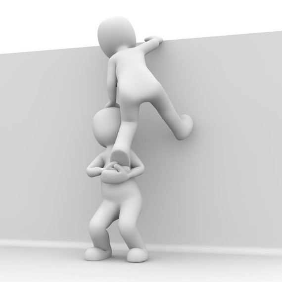 A black and white computer generated image of two faceless humanoid figures against a blank wall. One is boosting the other up and over the wall.