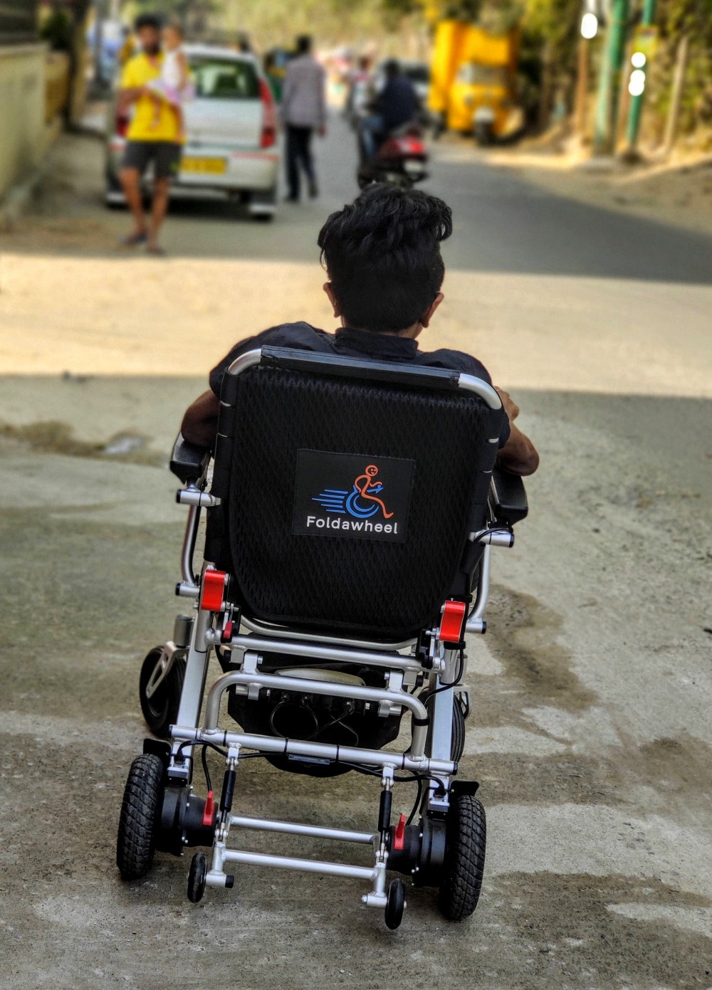 A person in a wheelchair with his back facing the camera. He is on the road, moving ahead in life