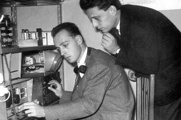 Two young men, one sitting and one leaning over, both listening to a machine on a table filled with equipment
