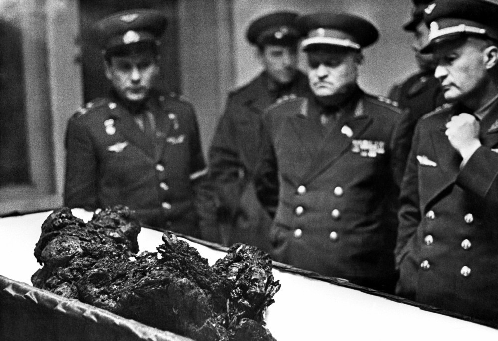 A molten rock sitting on a white table, surrounded by men in uniform