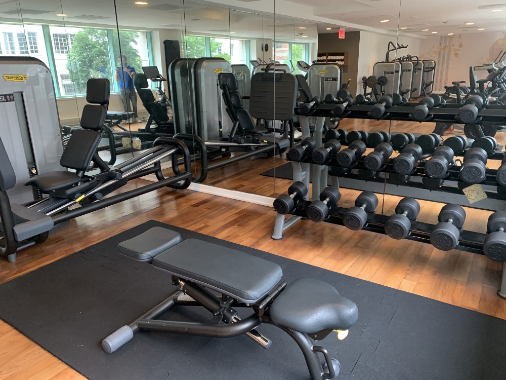 Park Hyatt Washington D.C.'s fitness center, which includes an adjustable bench, a set of dumbbells, and a leg press machine.