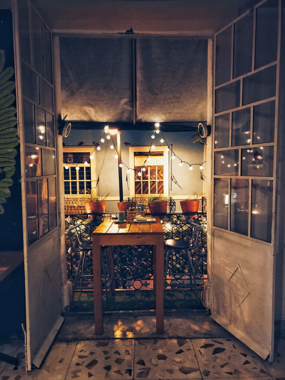 A private table and balcony for two surrounded by lights and spanish architecture.