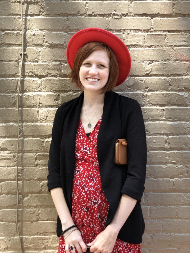 Photo of me in a red dress and black jacket wearing a red fedora