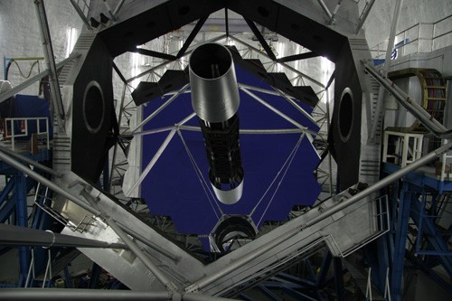 Looking down the hexagonal tube into the mirror assembly of a large telescope