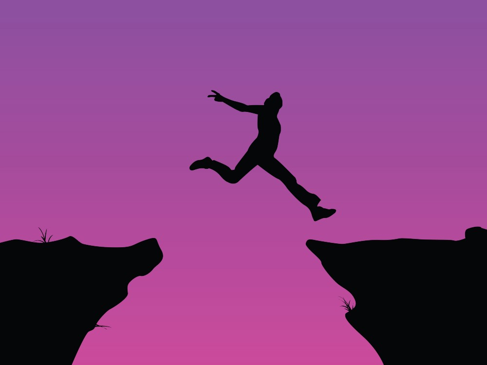 Person leaping across an opening between two cliffs. Silhouetted agains pink sky.