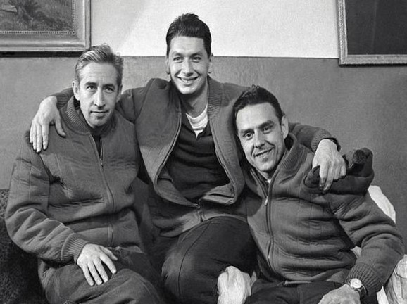 Three men pose with their arms around each other in matching jackets, smiling