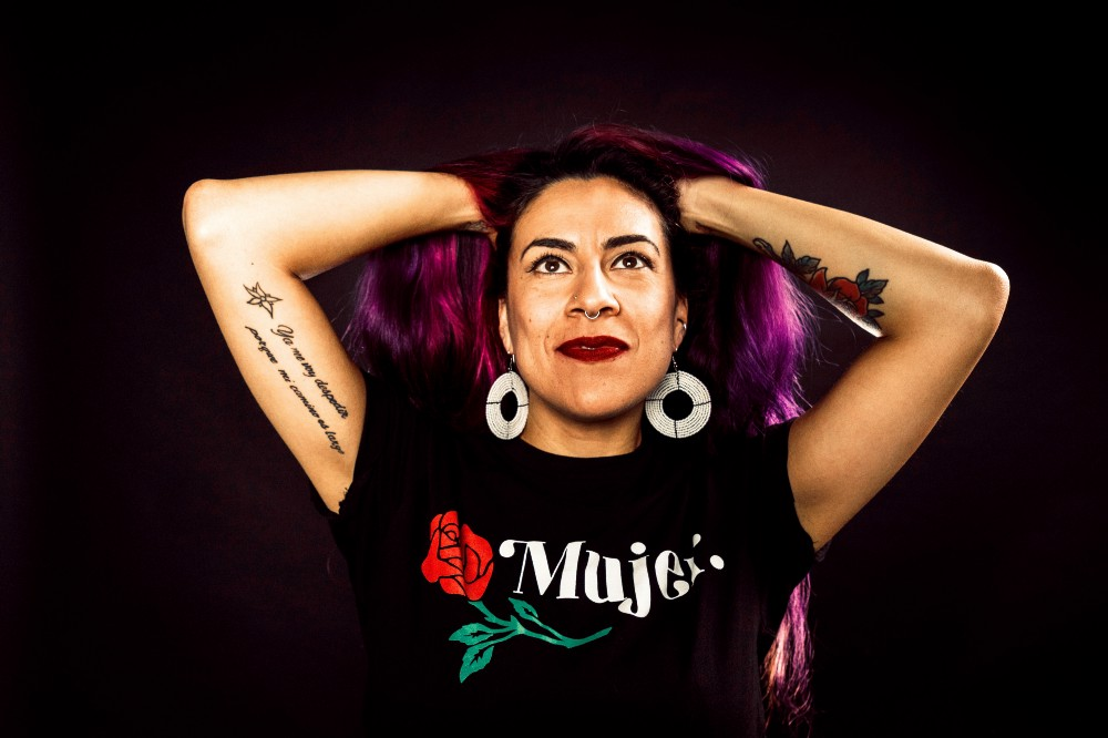 Woman against a black background with her hands in her purple hair