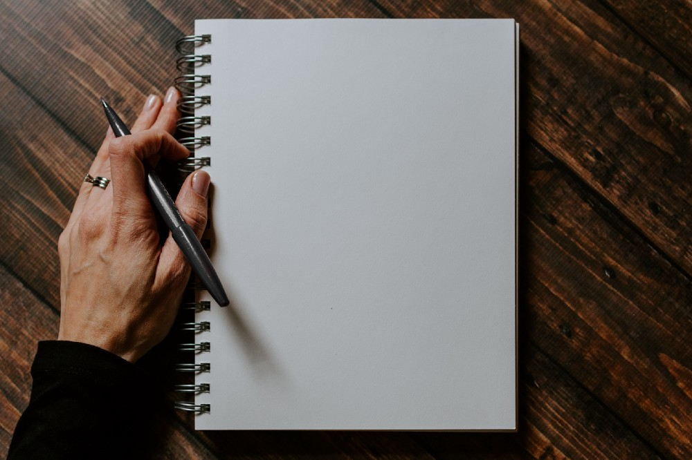 picture of an empty page on a notepad and a pen held by a woman