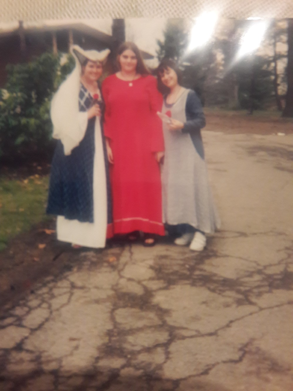 Three young women standing in renaissance dresses at an event.