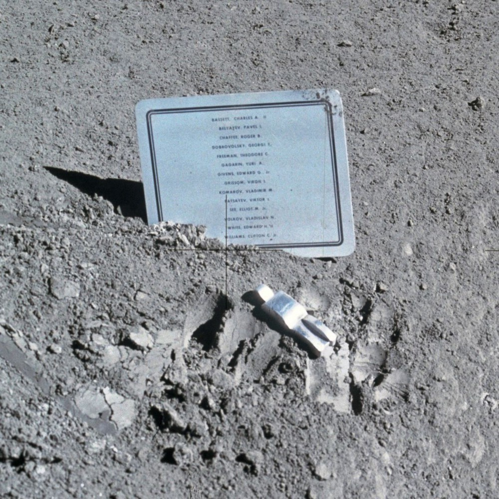 The rocky gray surface of the moon, a small silver astronaut sculpture on the ground in front of it, face down, and a plaque with a list of names
