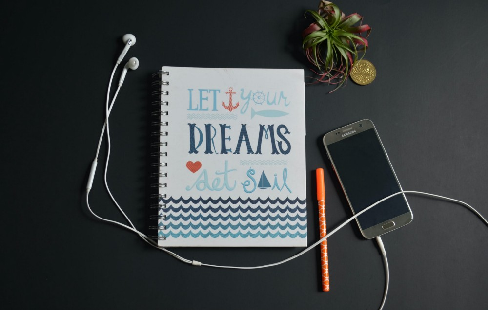 """A mobile phone with attached headphones accompanied by notebook with title that reads """"Let Your Dreams Set Sail."""""""