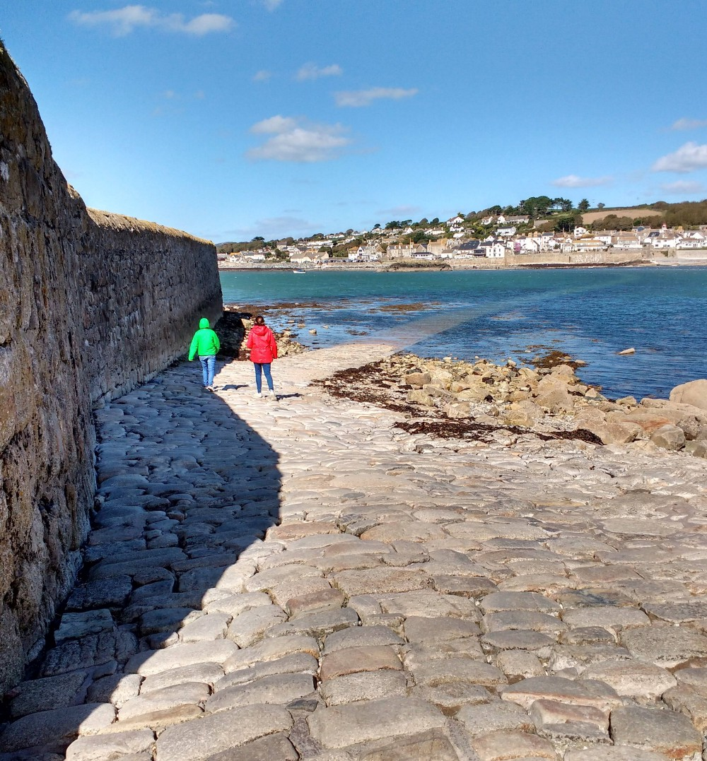 It shows two children on a cobbled road that disappears into the sea. It shows how a road can be difficult to follow.