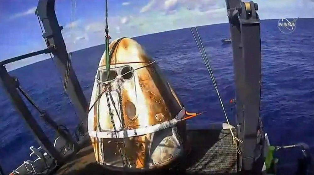 A burned space capsule is recovered from the ocean.
