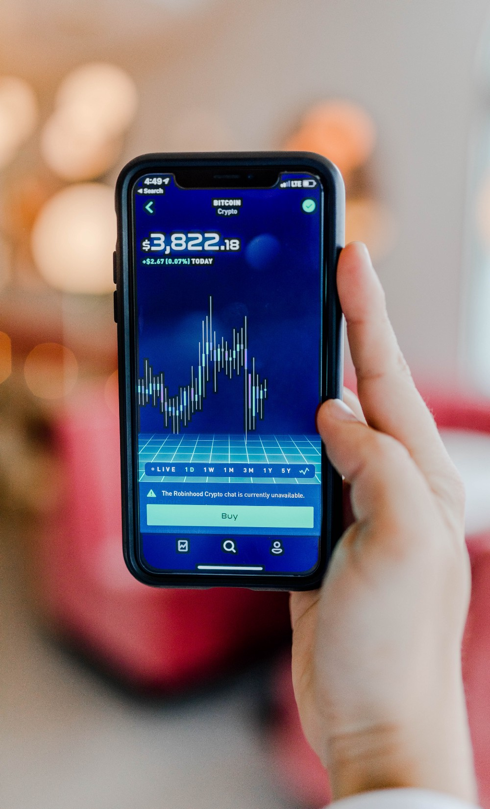 A phone with the chart of the price of the cryptocurrency, Bitcoin, on the screen on Robinhood platform.
