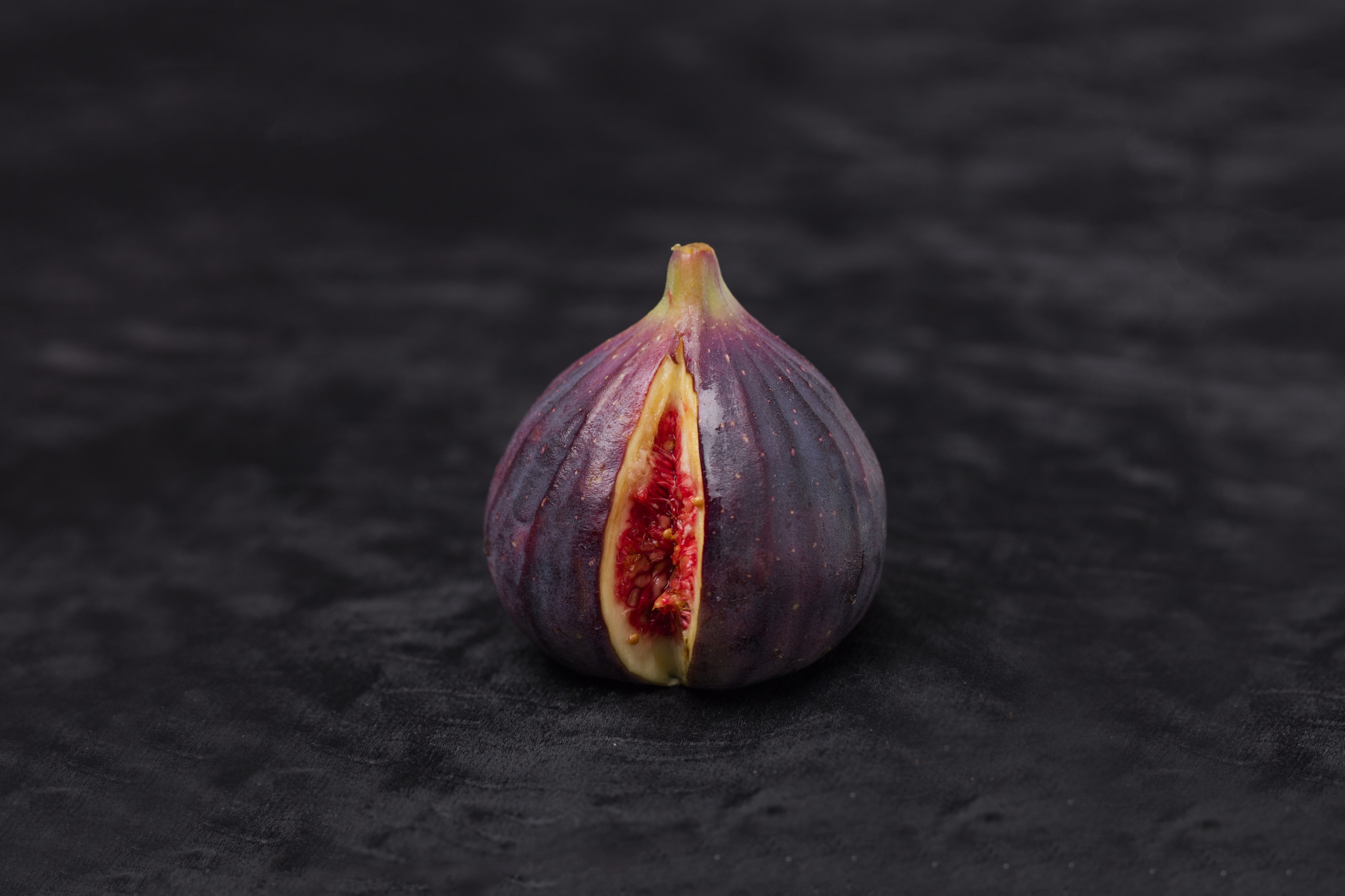 A single purple fig on a dark background with a small slice reveling the pink interior.