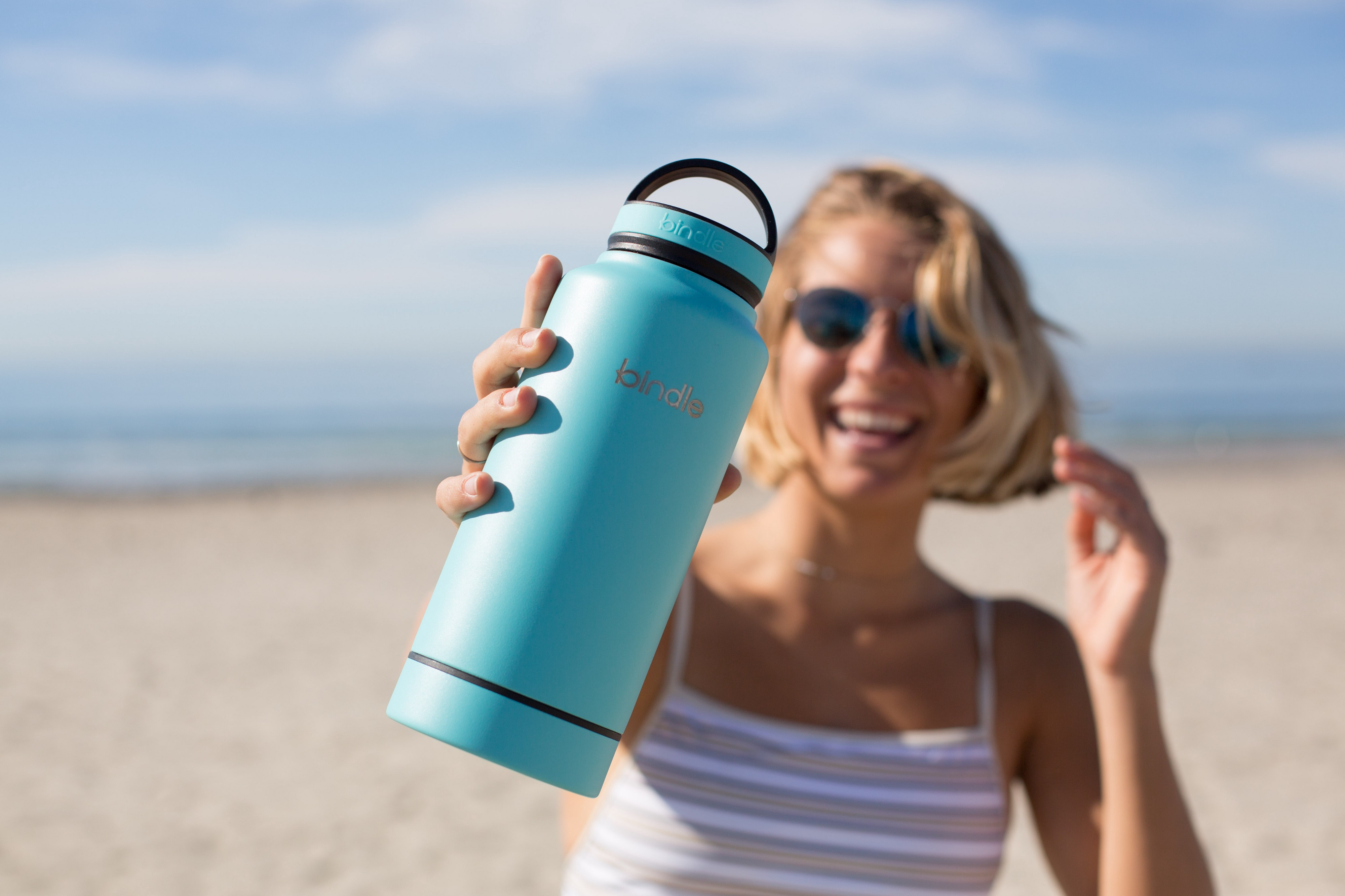 Woman holds reusable drink bottle on the beach.