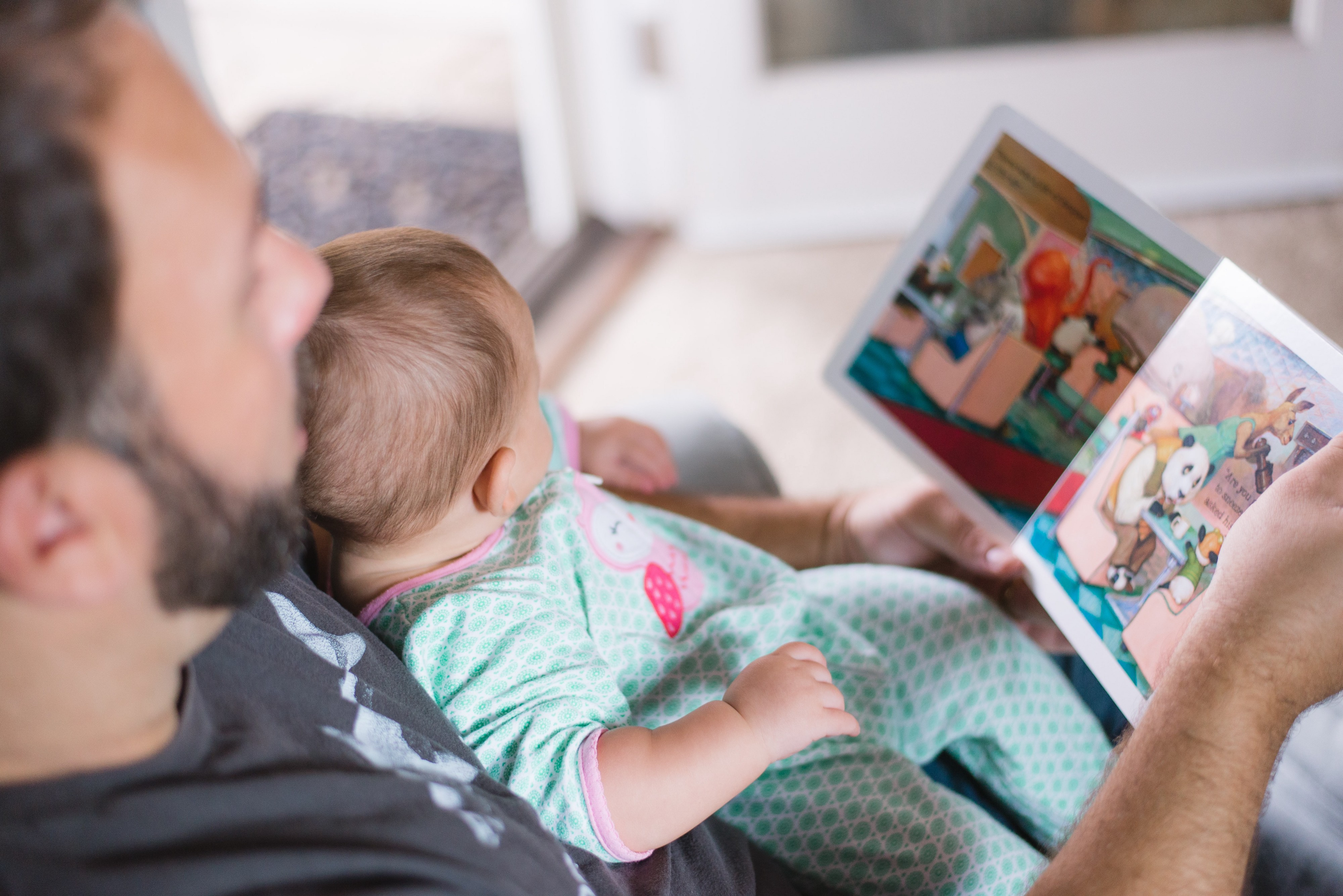 Man reads to his baby who is sitting in his lap.