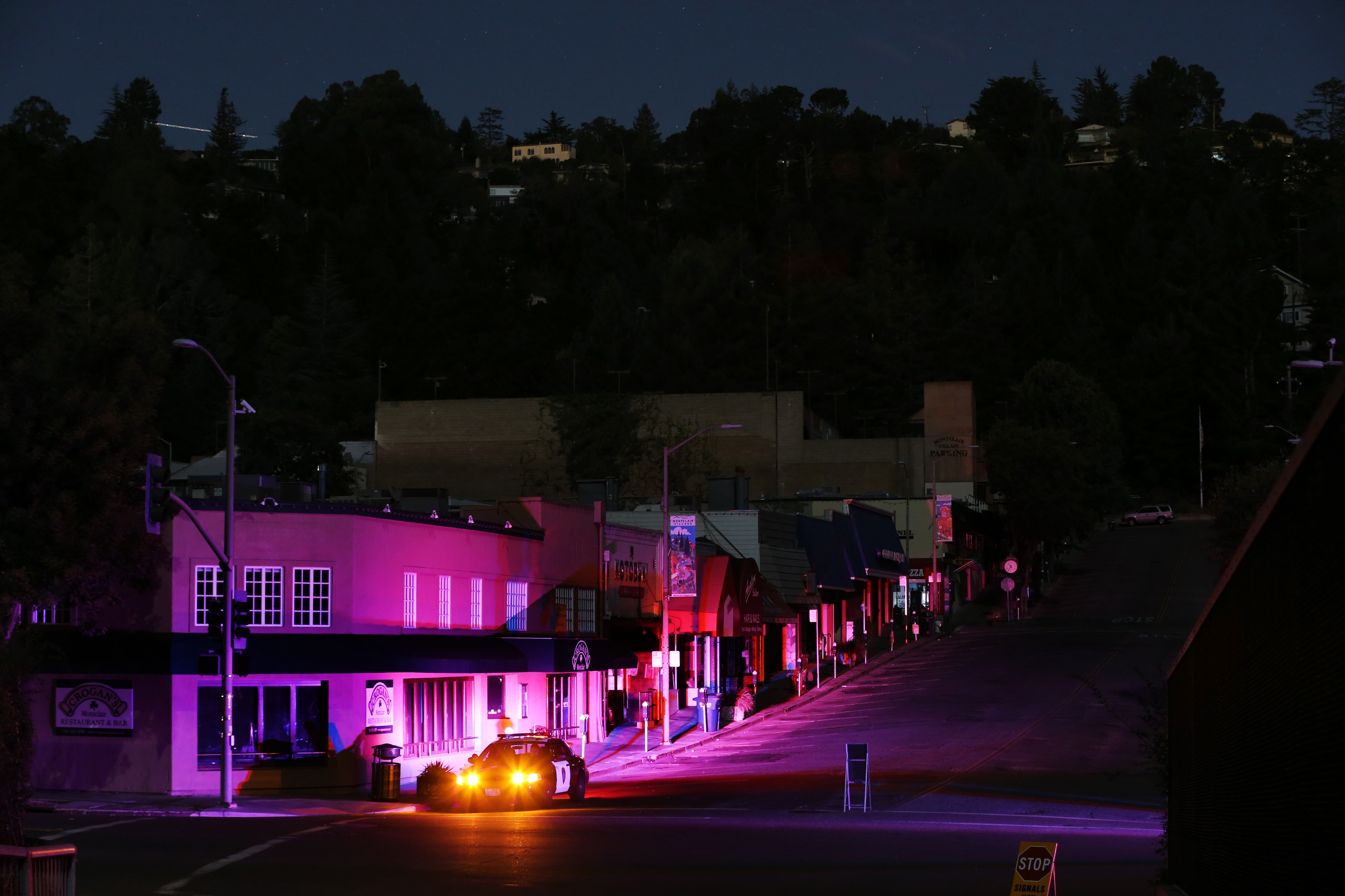 An Oakland police cruiser has its lights on in the Montclair shopping district during the PG&E California power outage.