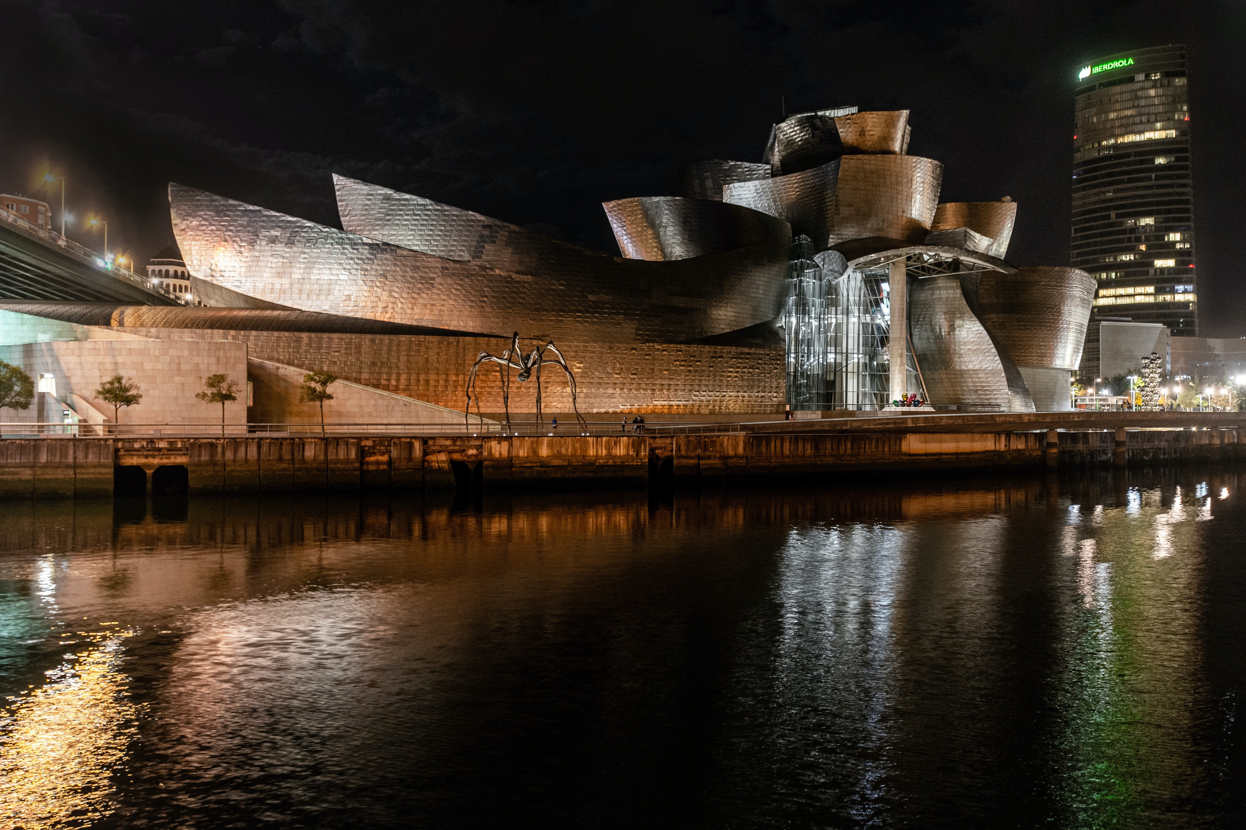 Nighttime photo of the Guggenheim Museum by the water in Bilbao, Spain