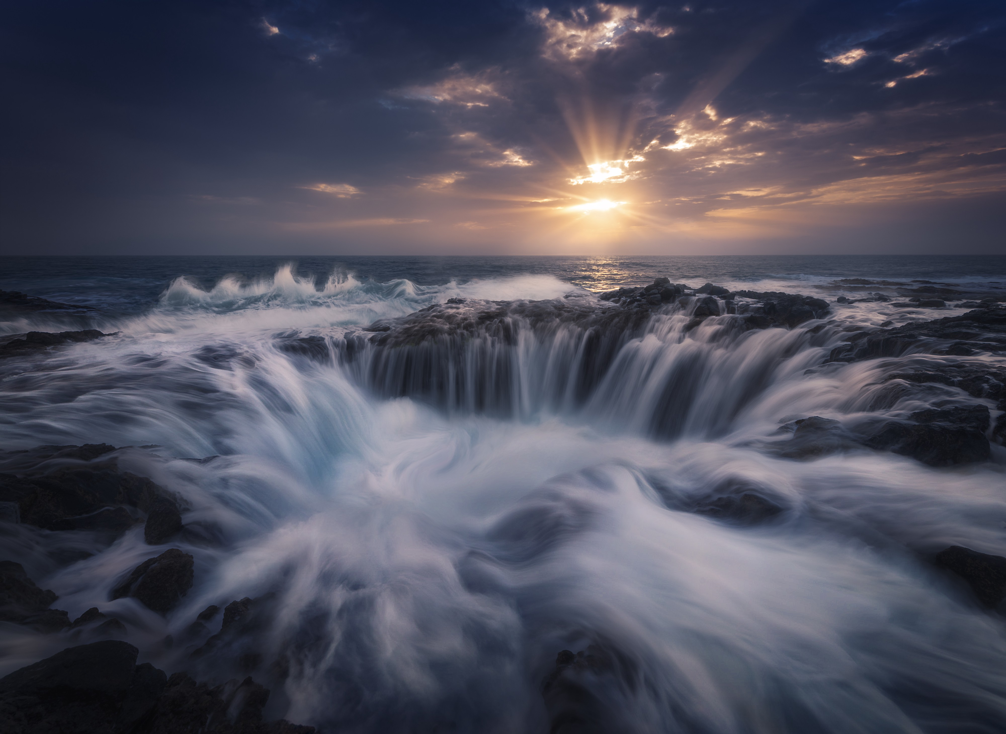 A seascape shows waves crashing in on eachother with white foam as the sun shines through some clouds in the background