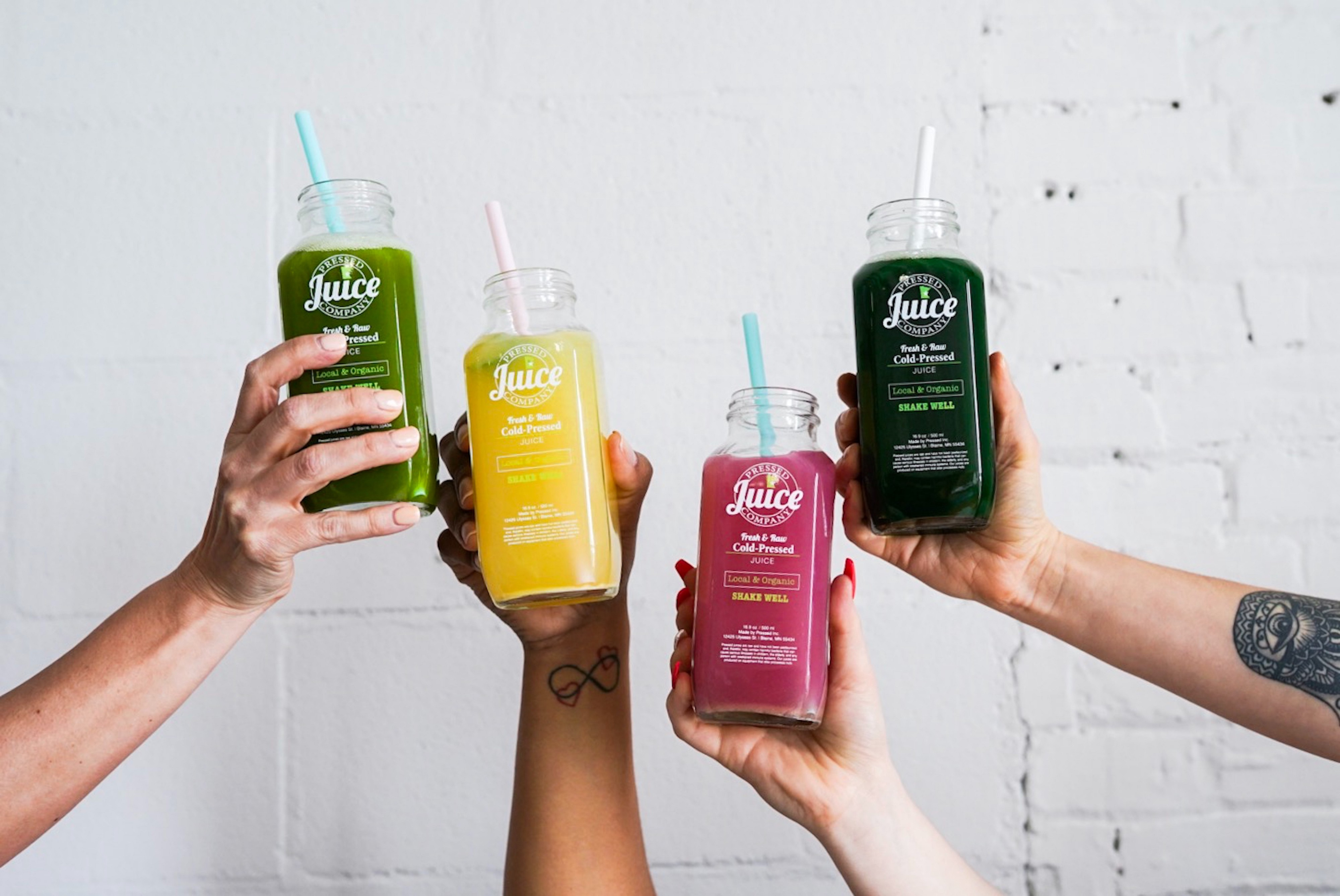 Photo of colourful juices in the cute bottles, held by hands.