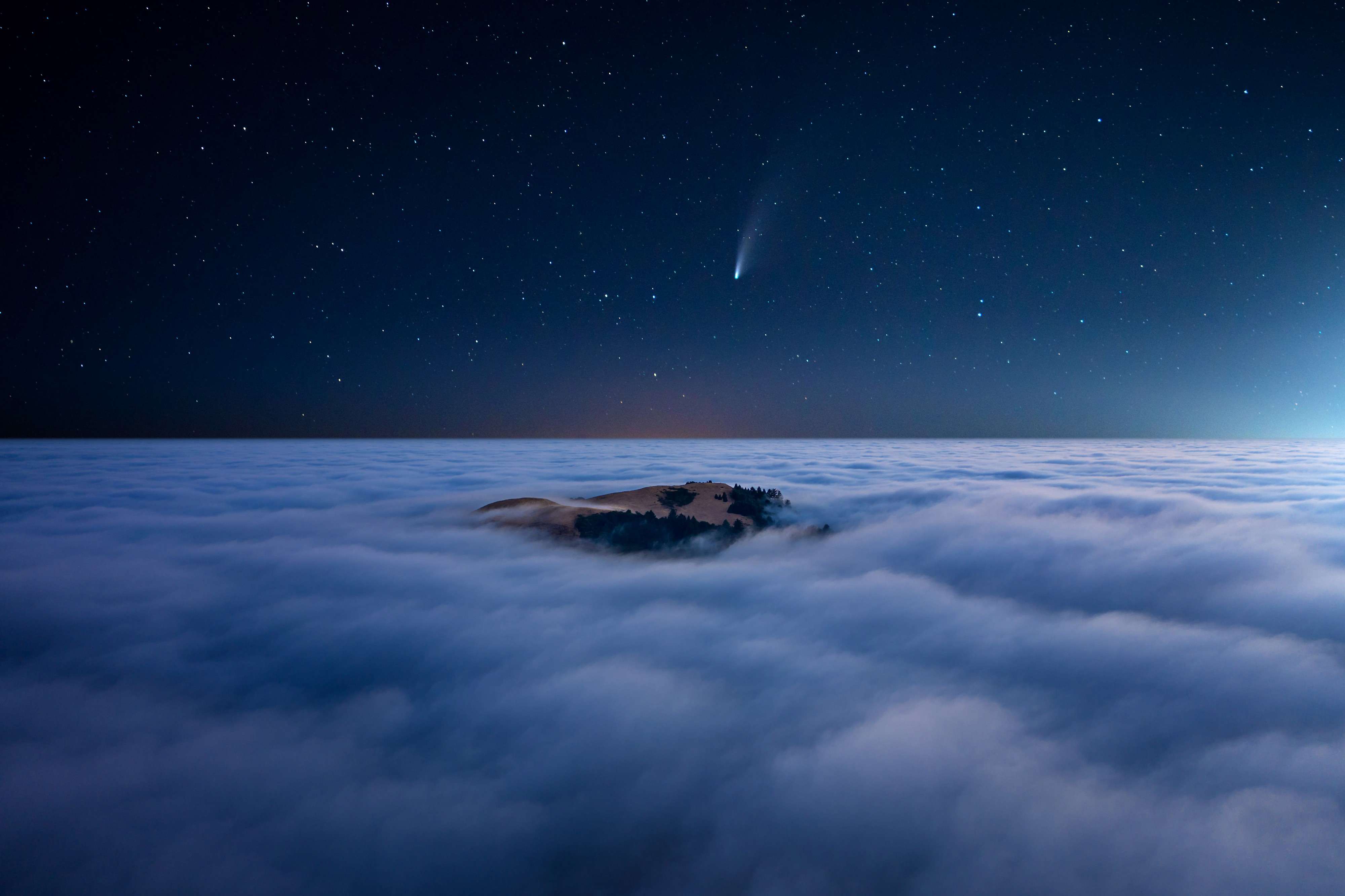 A comet or shooting star appears clearly in the sky above the clouds, which are broken in one spot showing beautiful earth