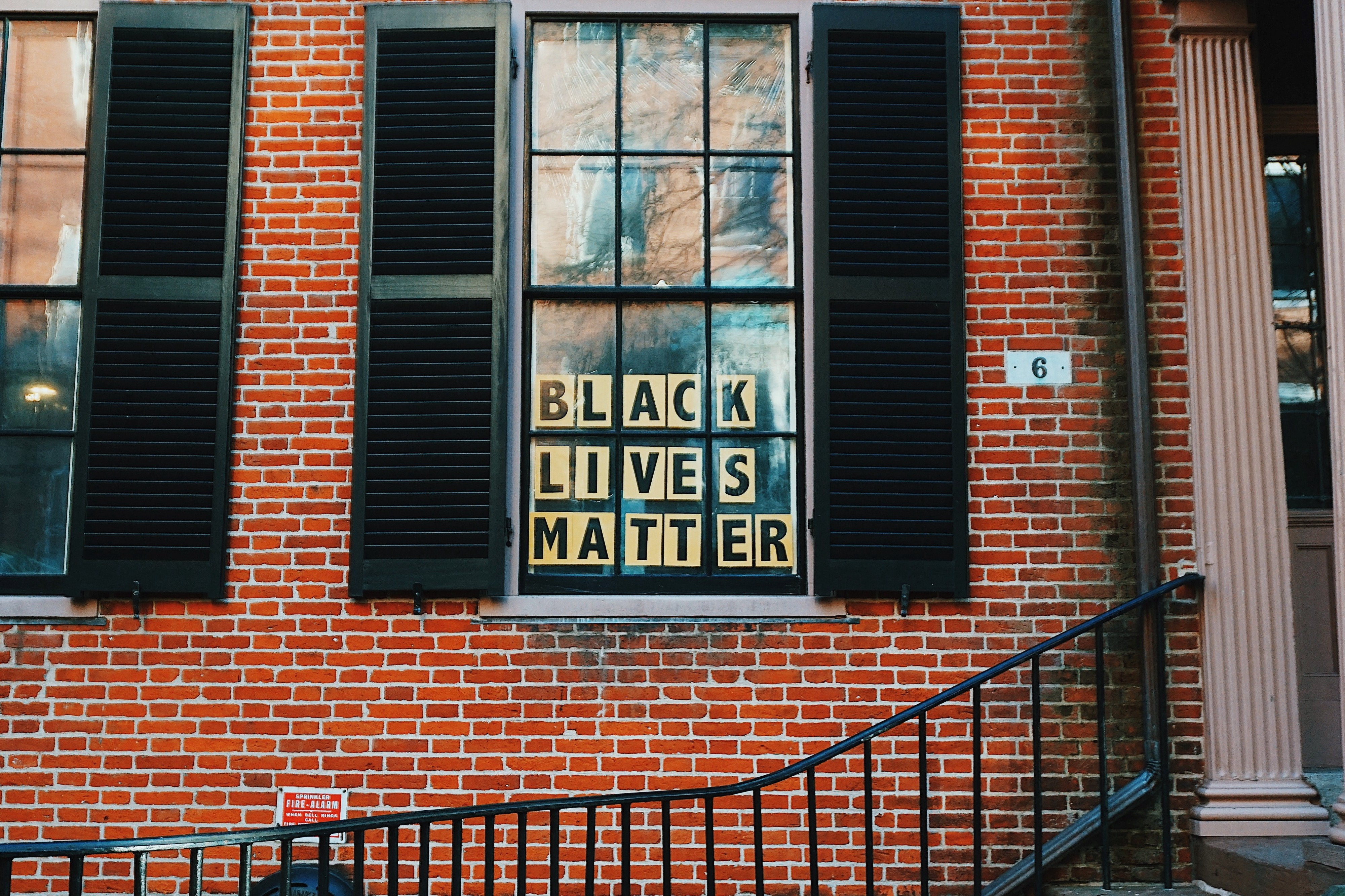 """BLACK LIVES MATTER"" on yellow paper in a window of a red brick building with black open shutters"