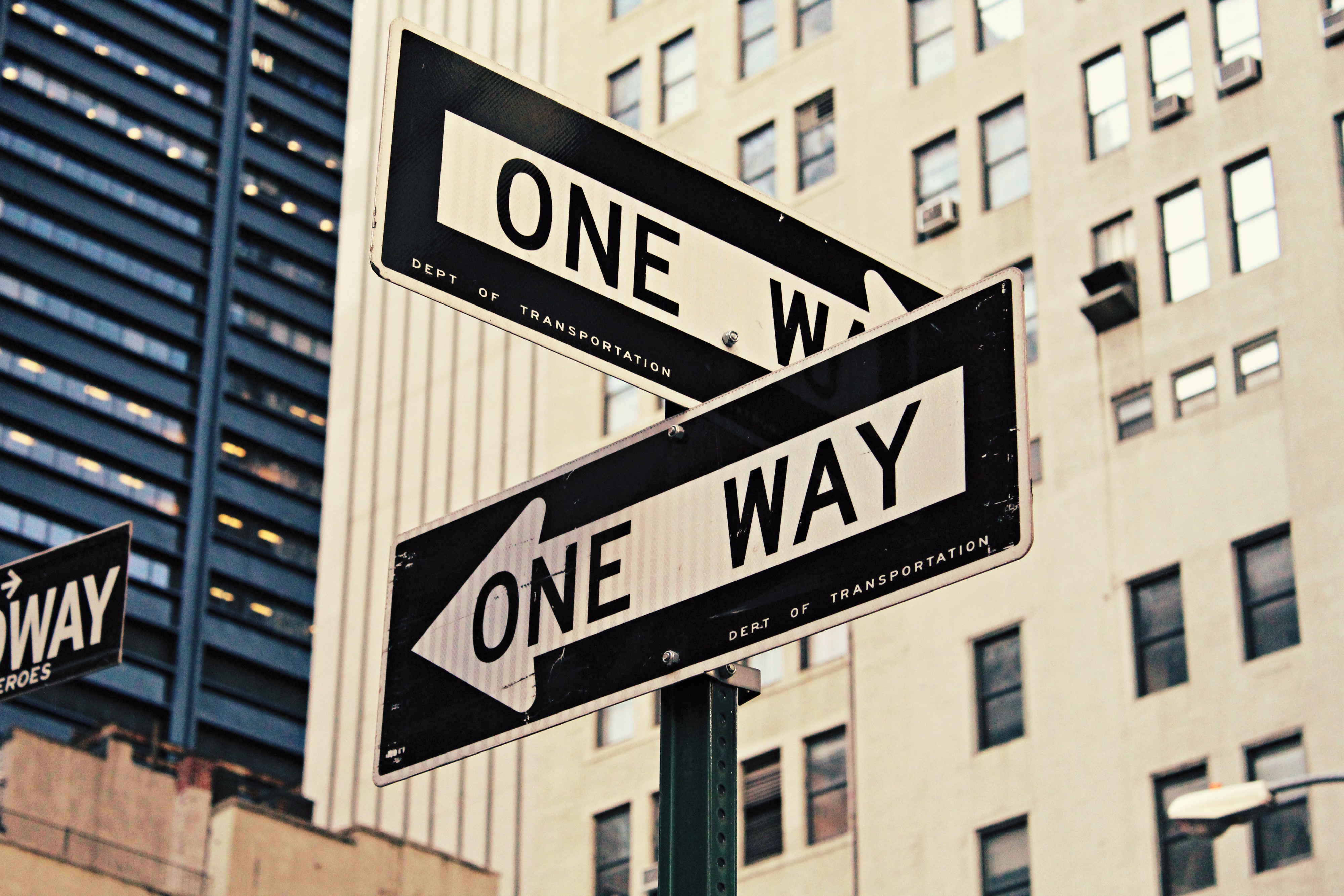 two one-way signs pointing to different streets at a city intersection