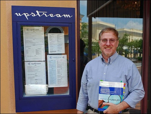 Image of Gary DePaul holding a copy of Rummler's Serious Performance Consulting book