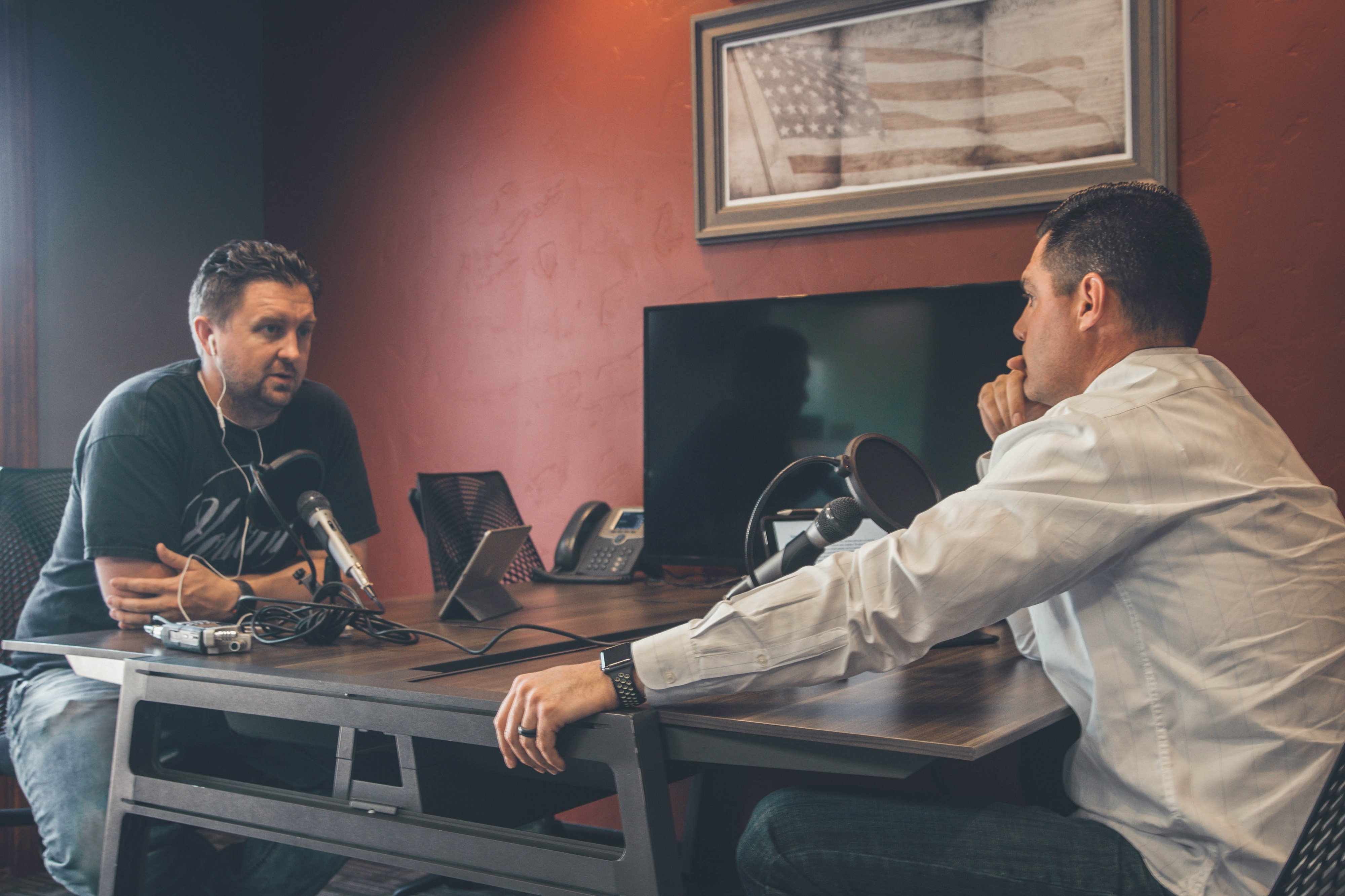 Two men at a table with miicrophones and headphones.