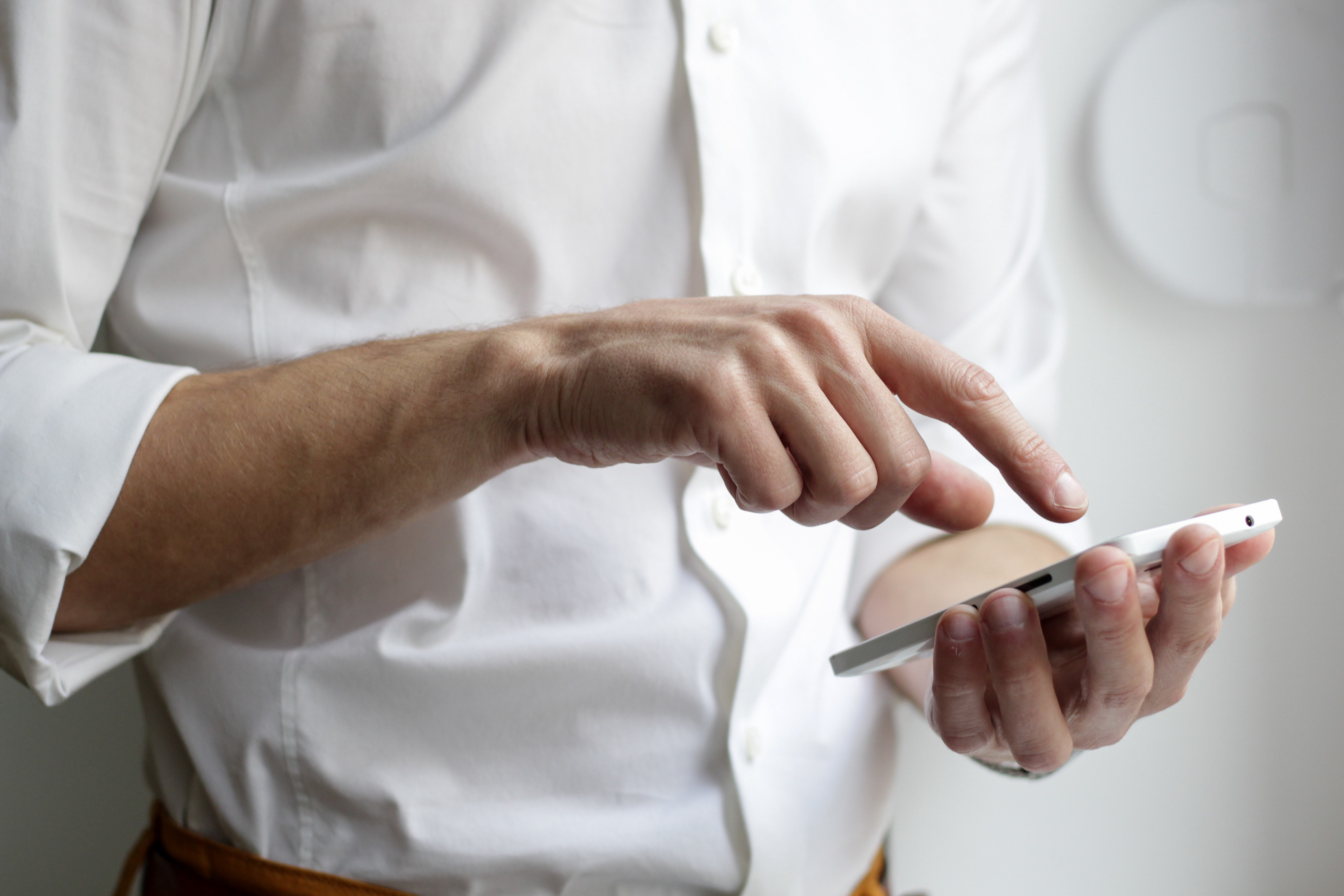 A man pointing his finger at a call to action button on his mobile phone.