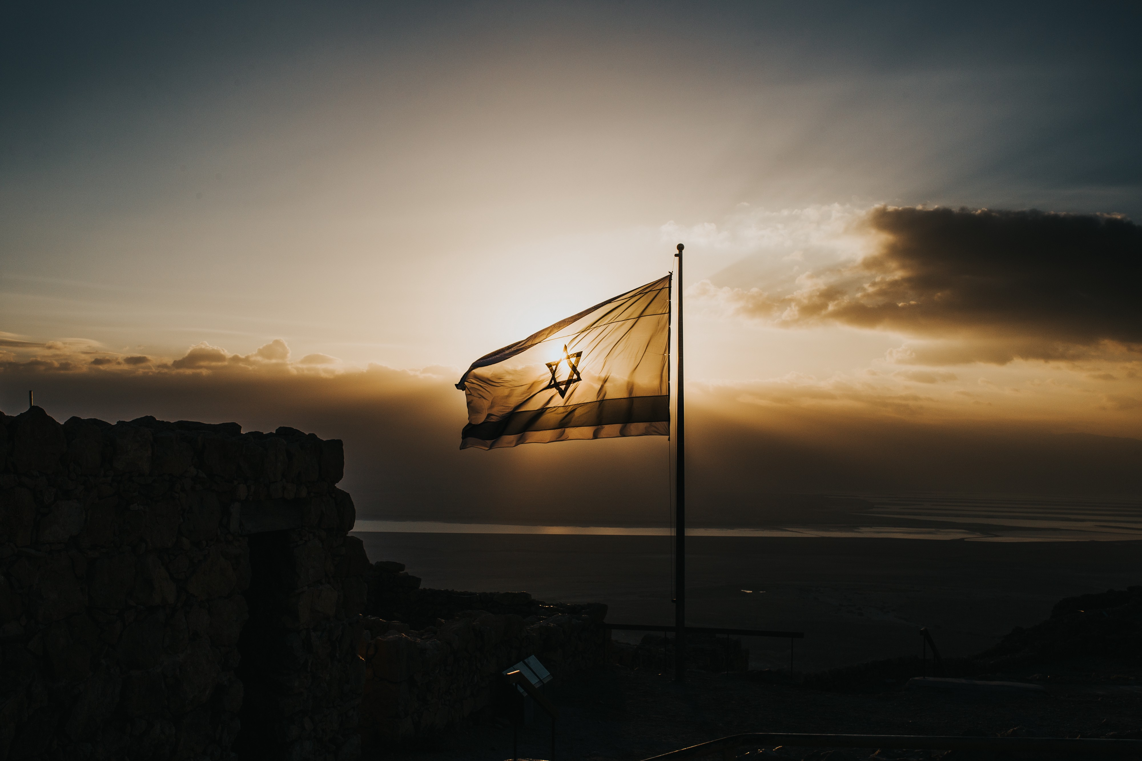 An Israeli flag waves in the wind against a dark sunset.