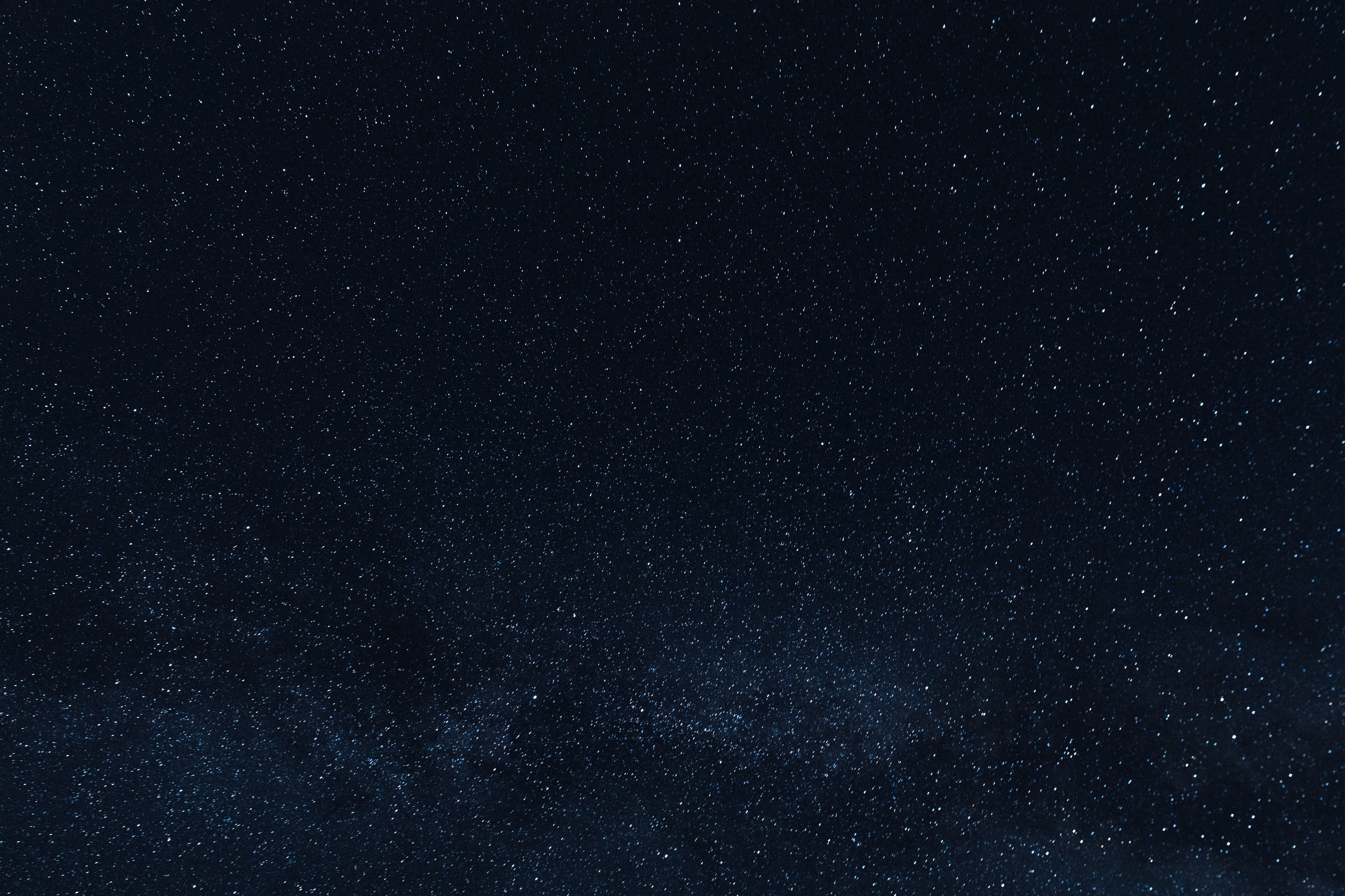 A wide view of a dark night sky, shot as though the viewer is looking up into the dim light of distant stars.