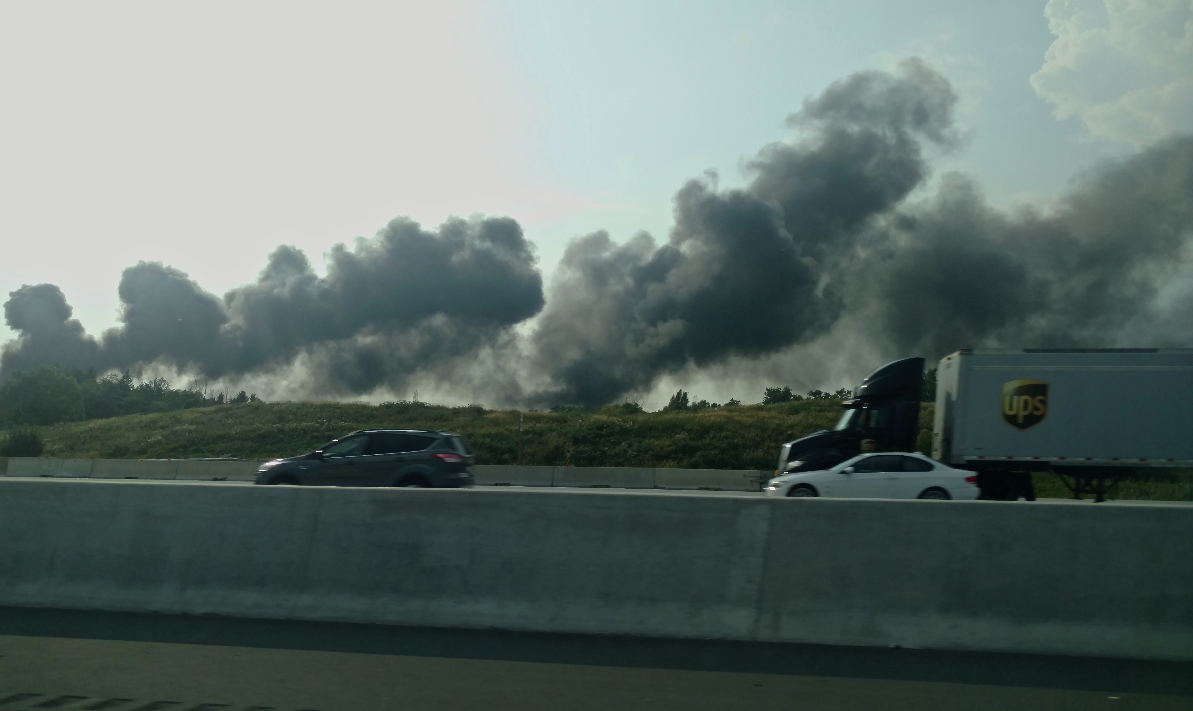 Two large plumes of smoke in the distance, with a busy highway in the foreground.