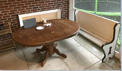 Two old white benches and a brown wood table