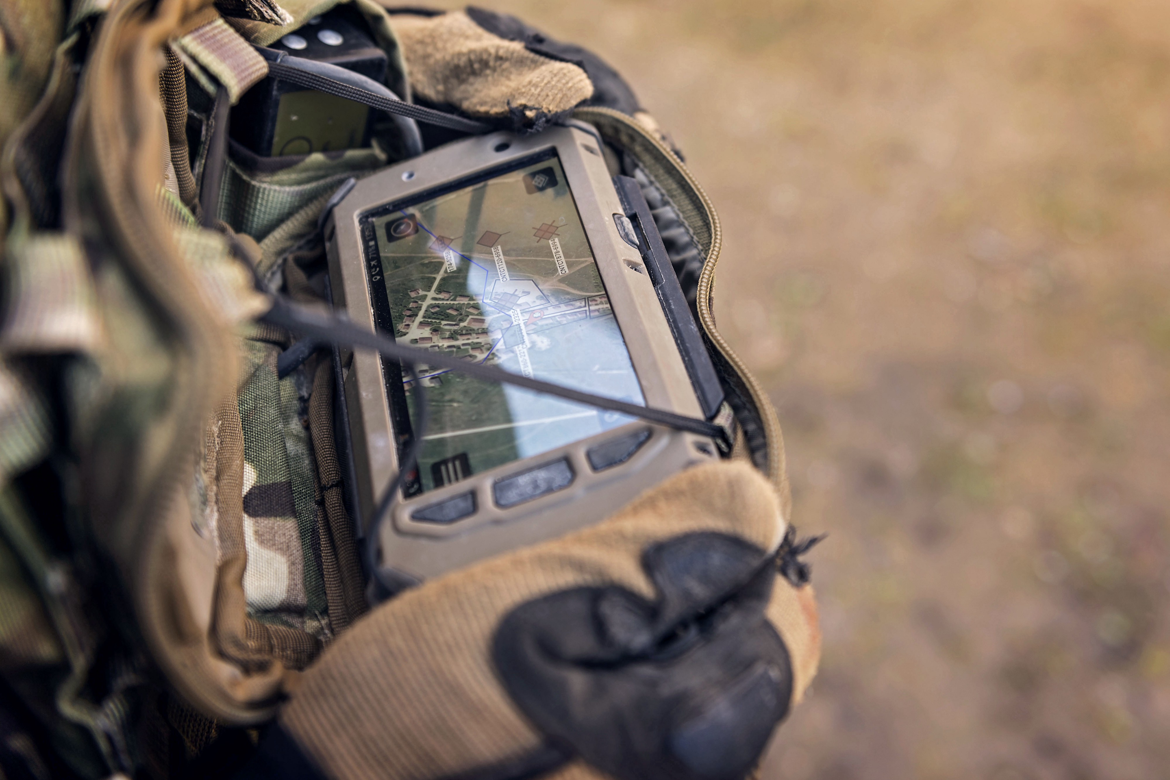 Soldier holding a piece of technology that shows the battle field on a small portable screen