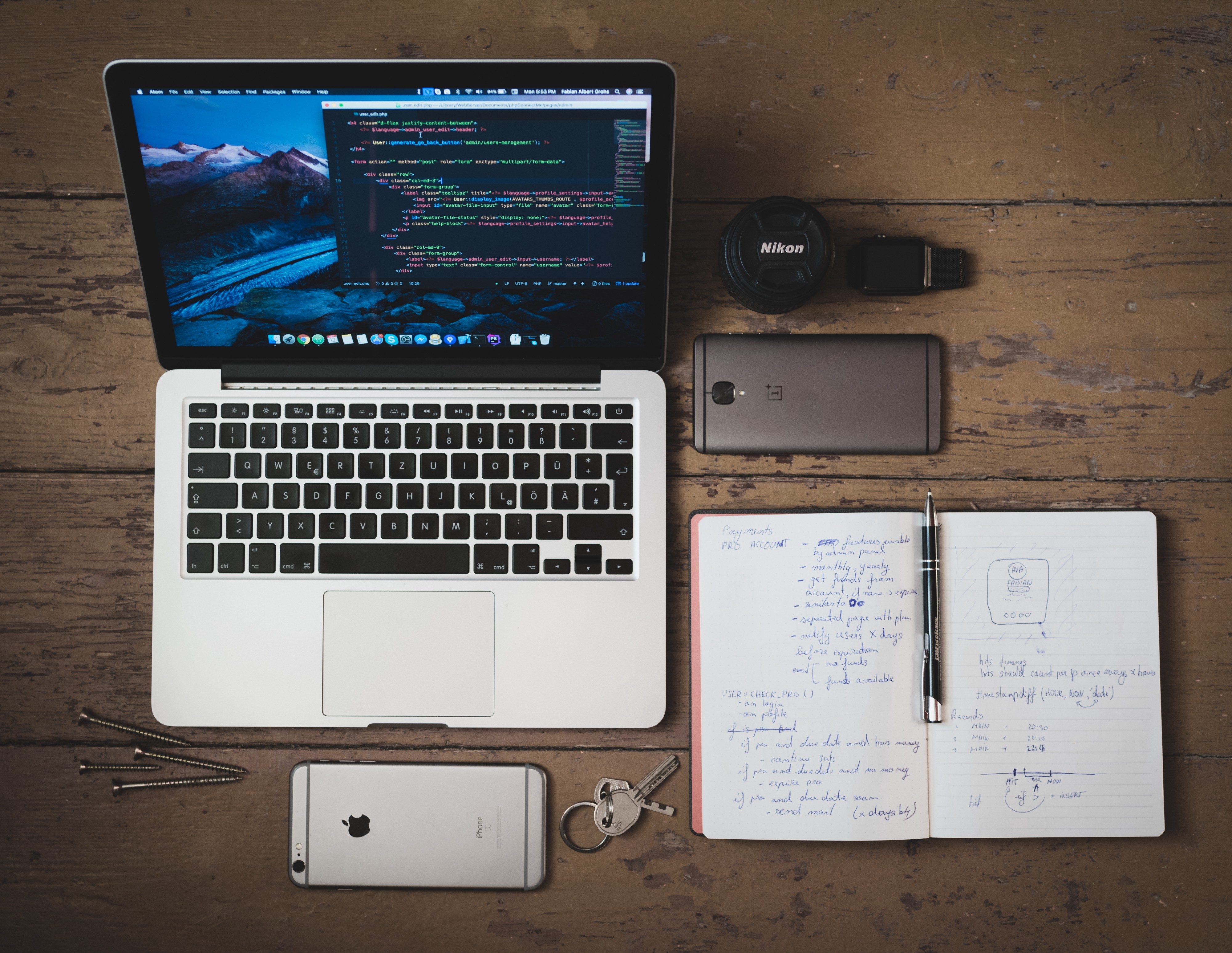 A programmers desk with his macbook, his phone, his smart watch and his drafting notebook.
